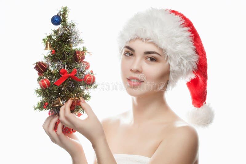 Retrato de una mujer hermosa en un sombrero rojo y con un árbol de navidad con las bolas de la Navidad y los arcos rojos foto de archivo