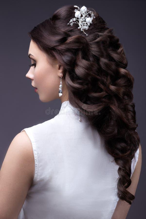 Retrato de una mujer hermosa en un vestido de boda en la imagen de la novia Opinión trasera del peinado fotografía de archivo