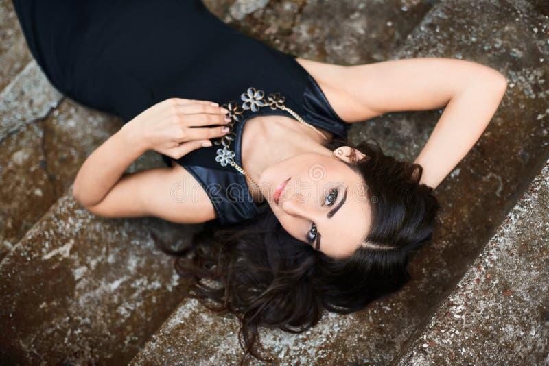 Retrato de una mujer hermosa en un vestido negro elegante que miente y que presenta en las escaleras foto de archivo libre de regalías