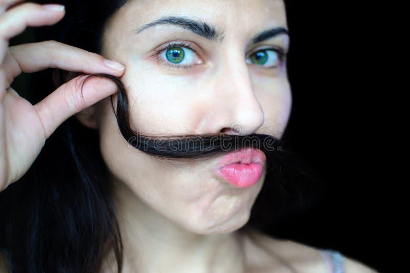 Retrato de una mujer hermosa joven con el pelo oscuro que sostiene un filamento de su pelo sobre su labio superior fotos de archivo libres de regalías