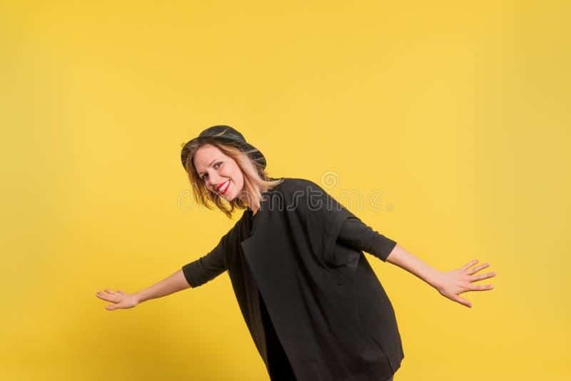 Retrato de una mujer hermosa joven con el sombrero negro en estudio en un fondo amarillo fotos de archivo libres de regalías