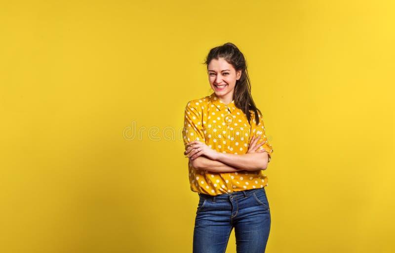 Retrato de una mujer hermosa joven en estudio en fondo amarillo imagen de archivo