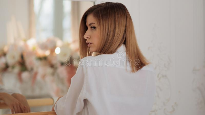 Retrato de una mujer hermosa joven en la barra del ballet Muchacha en la camisa blanca fotografía de archivo libre de regalías