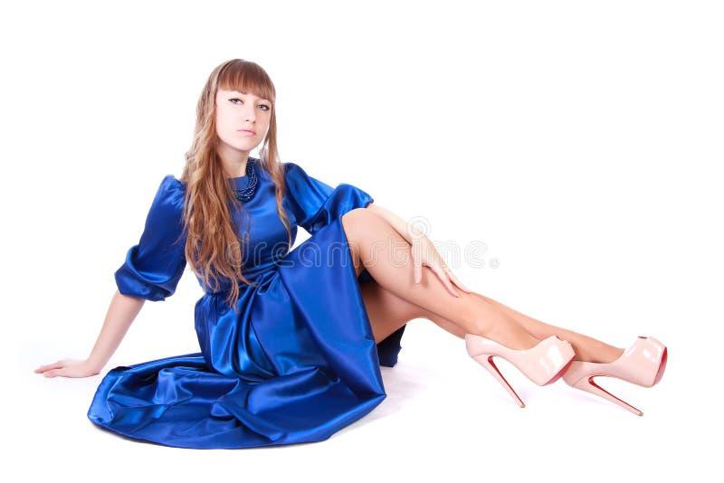Retrato de una mujer hermosa joven que se sienta en un Dr. azul de la tarde fotos de archivo