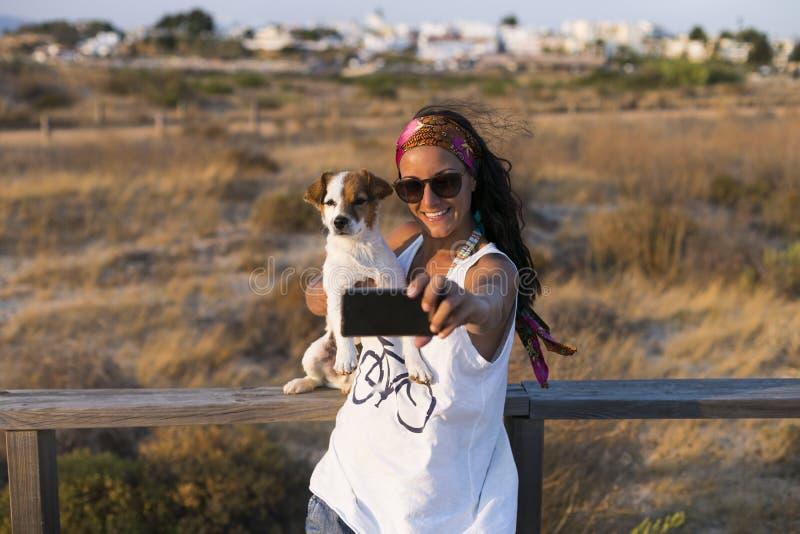 Retrato de una mujer hermosa joven que toma un selfie con él perro lindo y sonrisa Puesta del sol Verano, diversión y forma de vi fotos de archivo