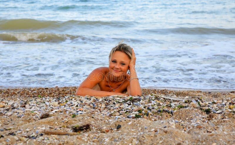 Retrato de una mujer hermosa que miente en la arena imagen de archivo