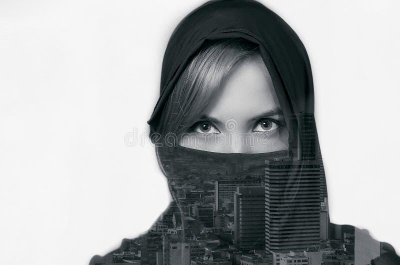 Retrato de una mujer hermosa sonriente que lleva un hijab con la exposición doble de un paisaje de la ciudad en hijab, en un blan imágenes de archivo libres de regalías