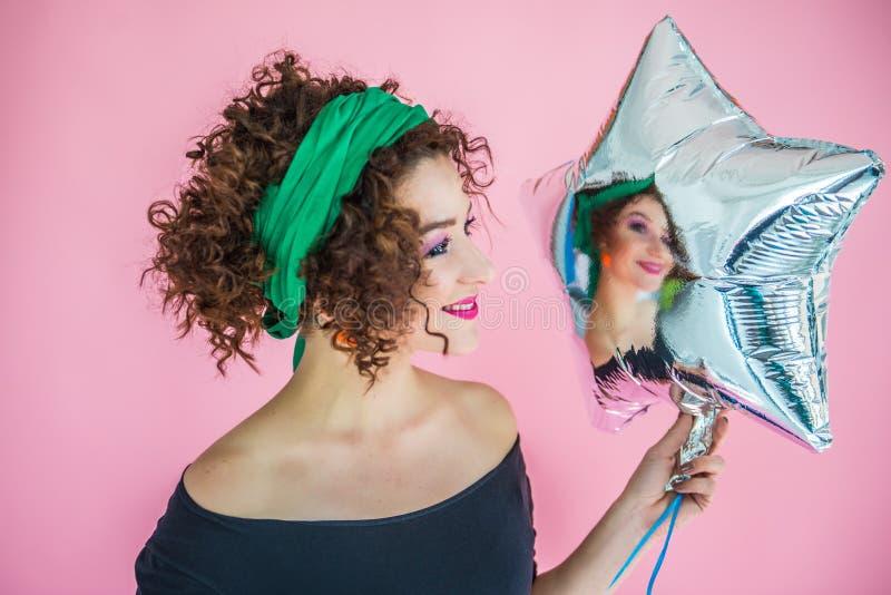 Retrato de una mujer joven de 30 a 35 años en anticipación a la fiesta sosteniendo una brillante bola inflable en forma de estrel fotos de archivo libres de regalías
