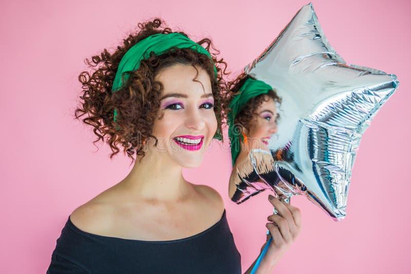 Retrato de una mujer joven de 30 a 35 años en anticipación a la fiesta sosteniendo una brillante bola inflable en forma de estrel fotos de archivo