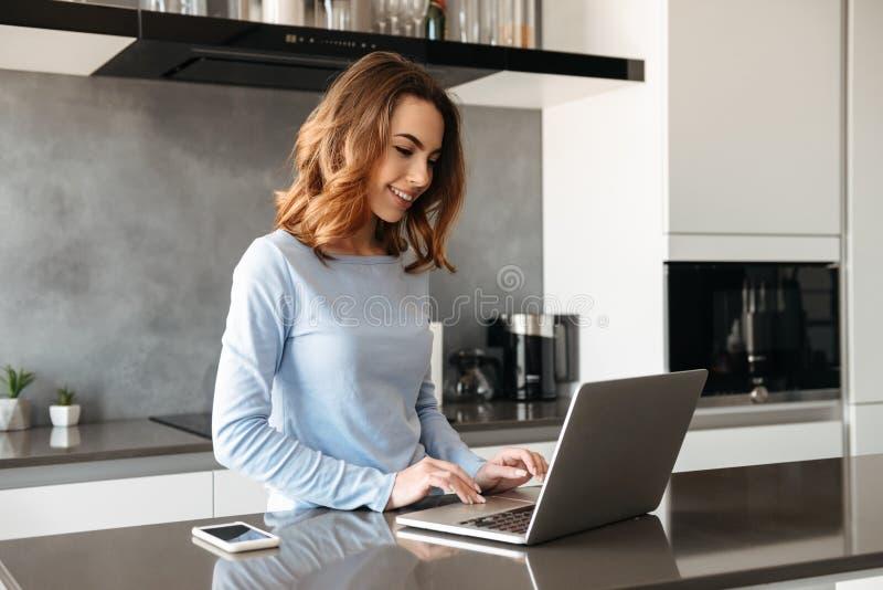 Retrato de una mujer joven alegre que usa el ordenador portátil fotografía de archivo