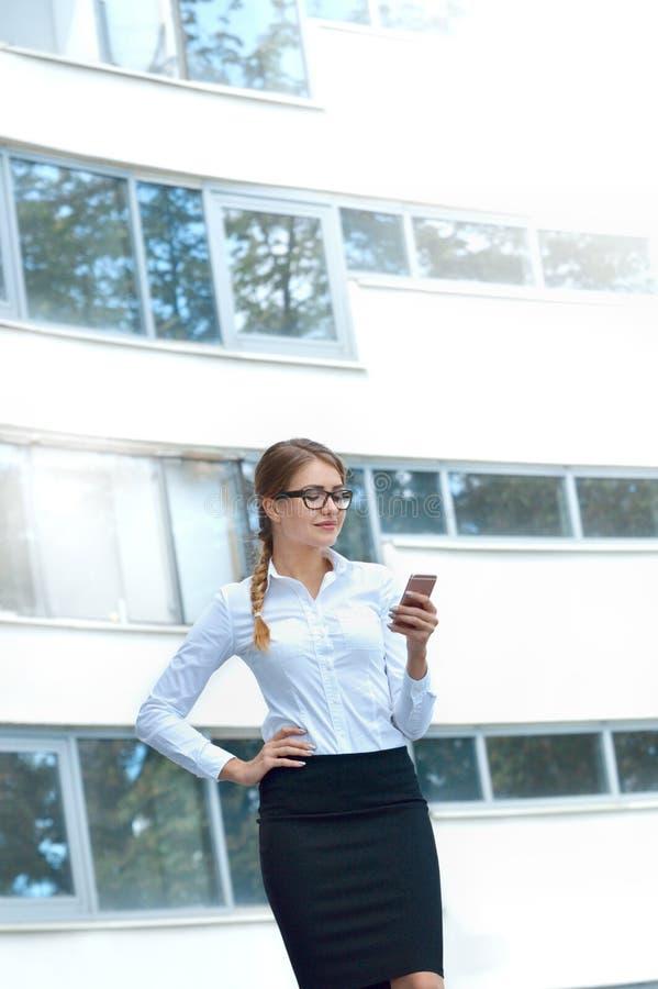 Retrato de una mujer joven atractiva que camina y que mira el teléfono móvil imagenes de archivo