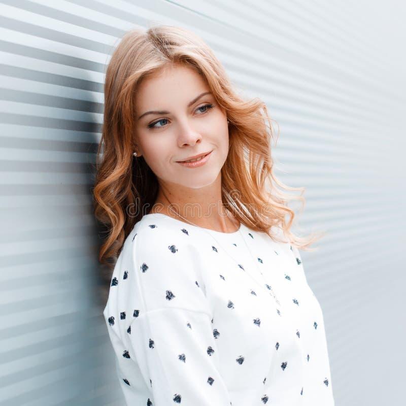Retrato de una mujer joven bastante atractiva con el pelo rizado rubio con los ojos azules en un suéter de moda cerca de la pared fotografía de archivo