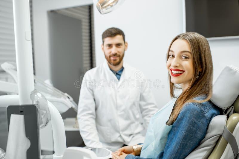 Retrato de una mujer joven con el dentista en la oficina dental fotos de archivo