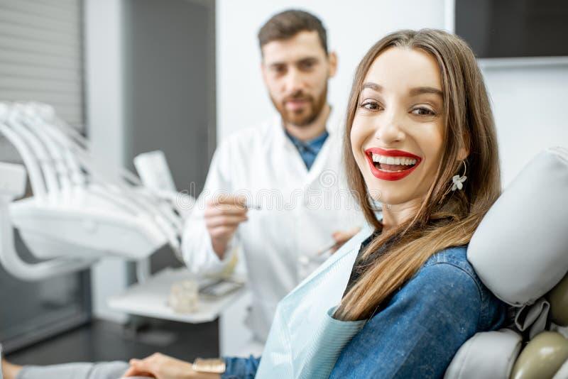 Retrato de una mujer joven con el dentista en la oficina dental imagen de archivo