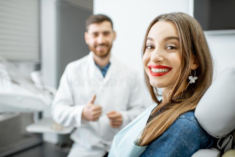 Retrato de una mujer joven con el dentista en la oficina dental fotos de archivo libres de regalías