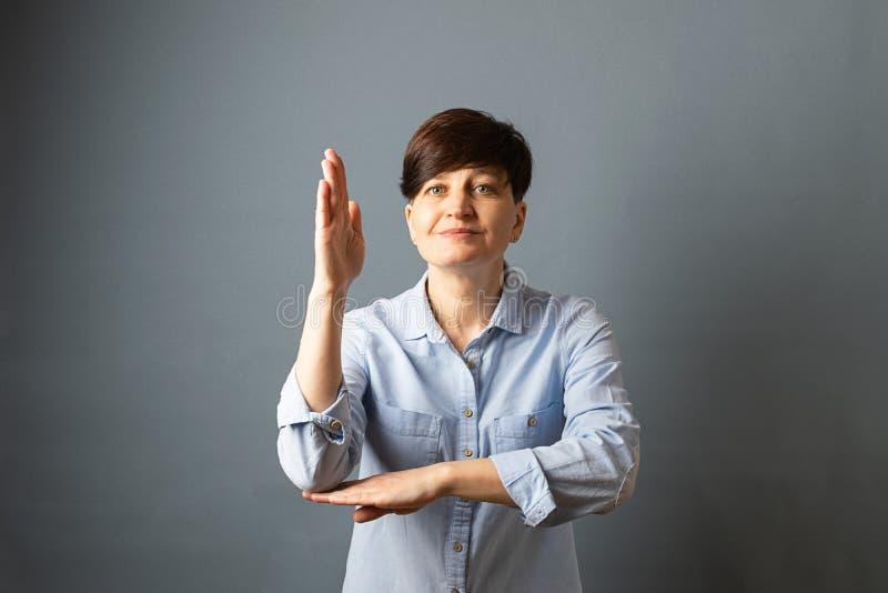 Retrato de una mujer joven con las manos de un corte del pelo corto para arriba en un fondo vacío gris Expresi?n facial de las em imagenes de archivo