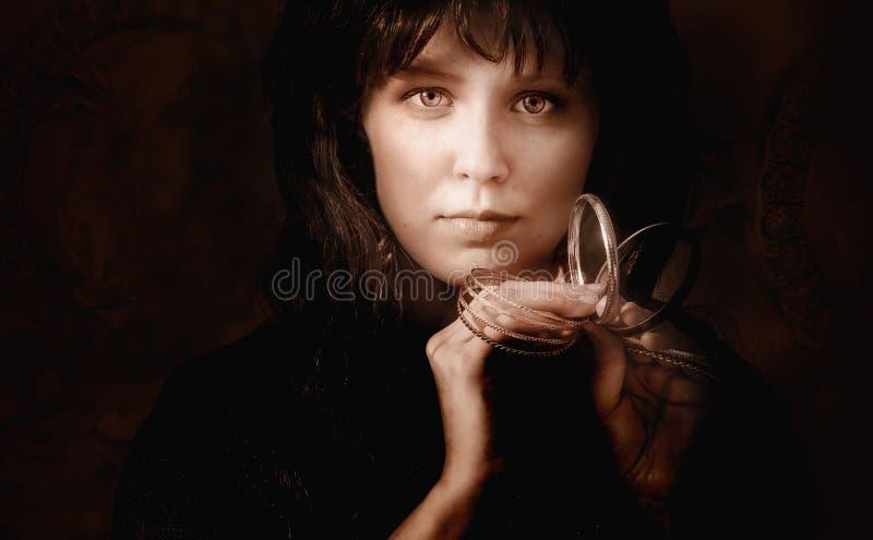 Retrato de una mujer joven con las pulseras de oro fotos de archivo