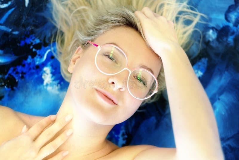 Retrato de una mujer joven con los vidrios y el pelo rubio con el fondo azul, las manos en su pelo foto de archivo libre de regalías