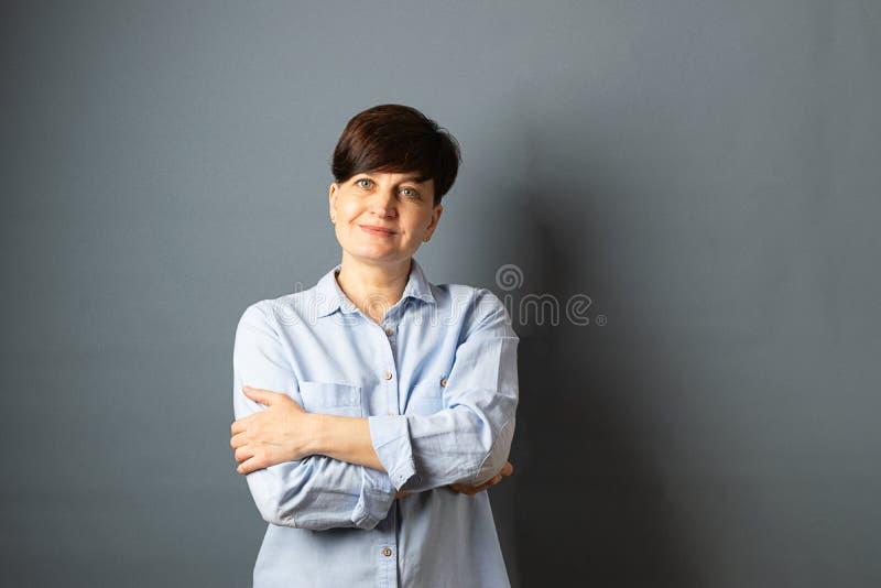 Retrato de una mujer joven con un corte de pelo corto en fondo en blanco gris Alegr?a humana de la felicidad de la expresi?n faci imágenes de archivo libres de regalías