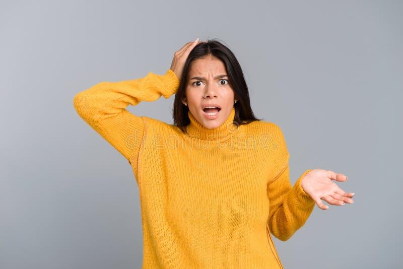 Retrato de una mujer joven confusa vestida en la situación del suéter aislado imagen de archivo