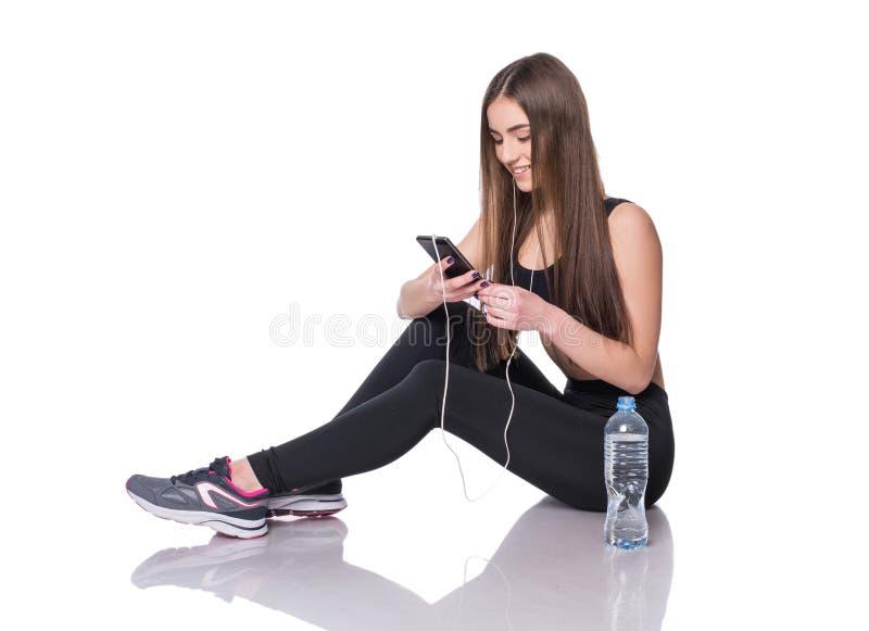 Retrato de una mujer joven del atleta que escucha la música con los auriculares sobre el fondo blanco Charla atractiva de la much foto de archivo
