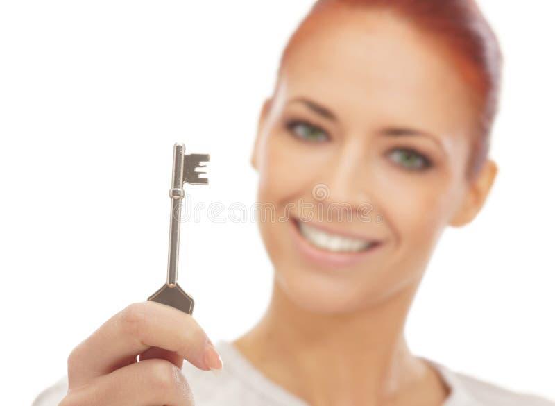 Retrato de una mujer joven del redhead que lleva a cabo un clave imágenes de archivo libres de regalías