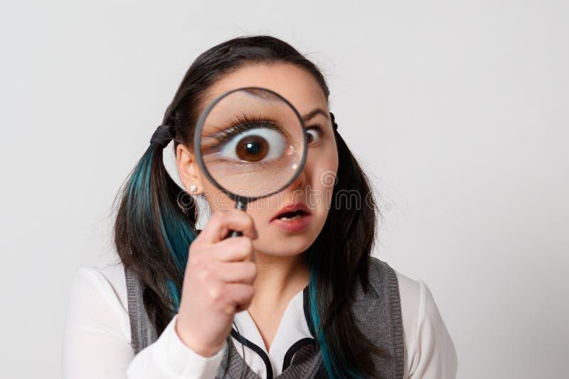 Retrato de una mujer joven divertida que mira la cámara a través de la lupa en fondo gris imagen de archivo