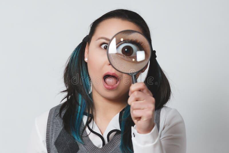 Retrato de una mujer joven divertida que mira la cámara a través de la lupa en fondo gris fotografía de archivo libre de regalías