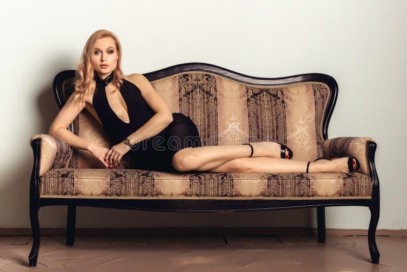 Retrato de una mujer joven elegante hermosa que presenta en un sofá antiguo fotografía de archivo