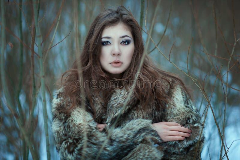 Retrato de una mujer joven en parque del invierno fotografía de archivo libre de regalías