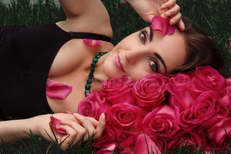 Retrato de una mujer joven en rosas en la hierba Retrato del arte fotografía de archivo