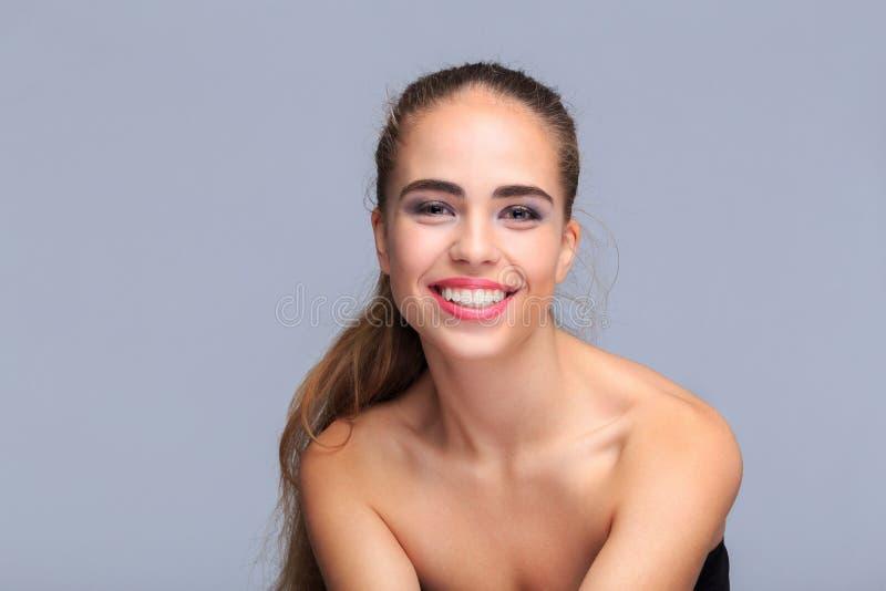 Retrato de una mujer joven en un fondo gris claro, sonriendo, cosméticos imagenes de archivo