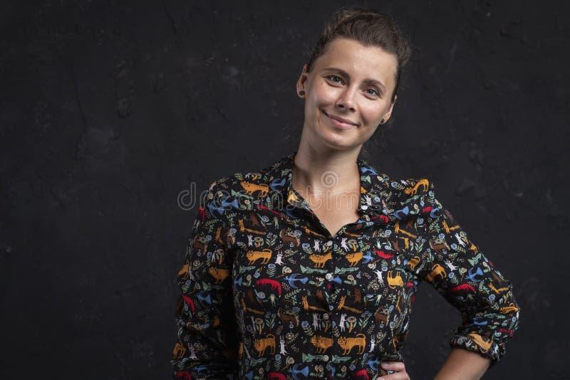 Retrato de una mujer joven en un fondo negro Muchacha natural atractiva en una camisa negra Muchacha del tiro del estudio que mir imagenes de archivo