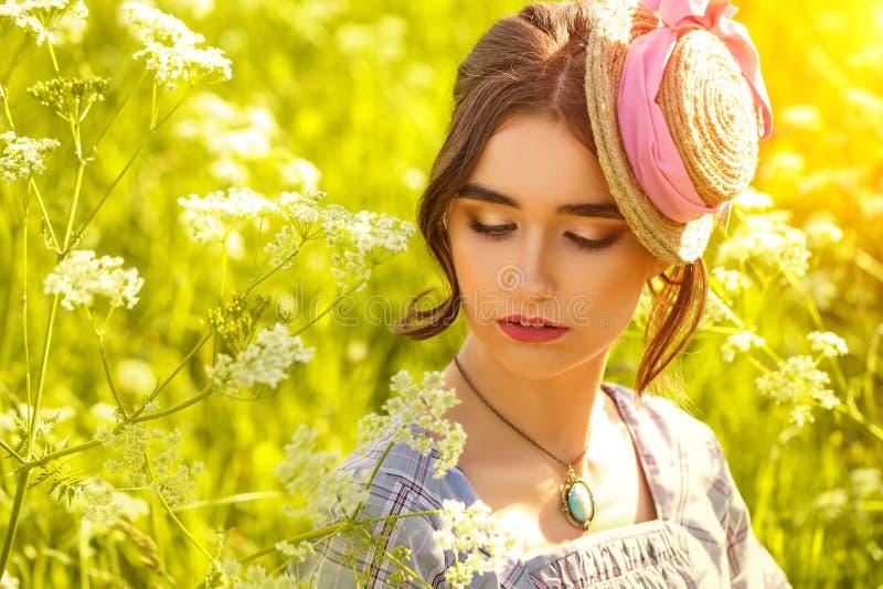 Retrato de una mujer joven en un sombrero en la hierba fotografía de archivo libre de regalías