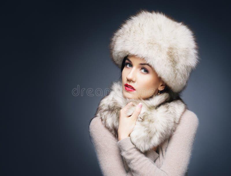 Retrato de una mujer joven en un sombrero peludo del invierno foto de archivo