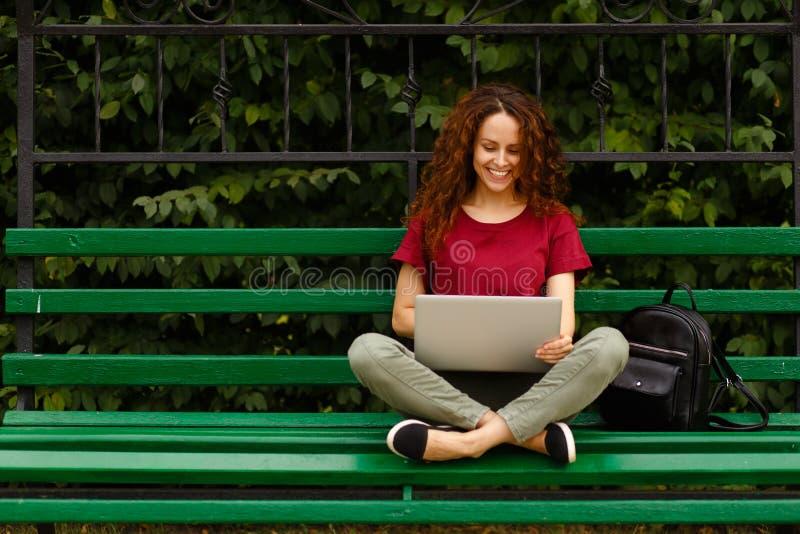 Retrato de una mujer joven feliz que sonríe usando el ordenador portátil, sentándose en banco en parque Concepto de la forma de v fotografía de archivo