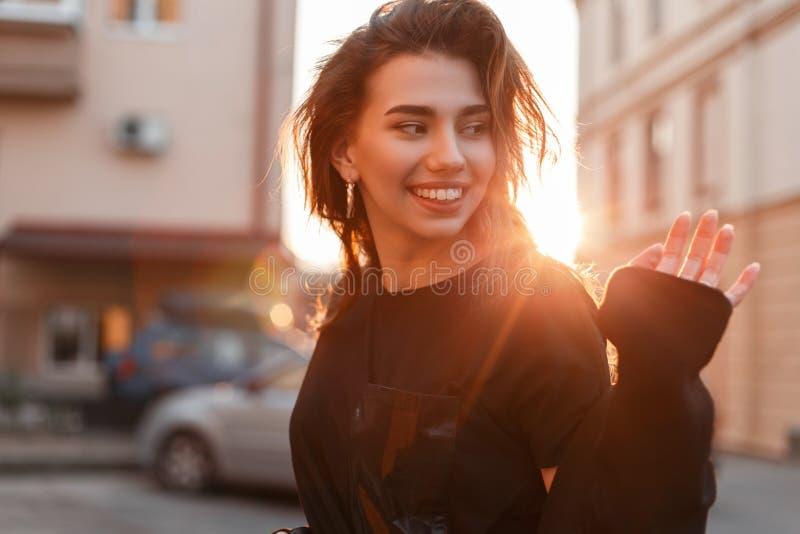 Retrato de una mujer joven hermosa bastante feliz con una sonrisa linda en una camiseta negra de moda al aire libre en la ciudad fotografía de archivo libre de regalías