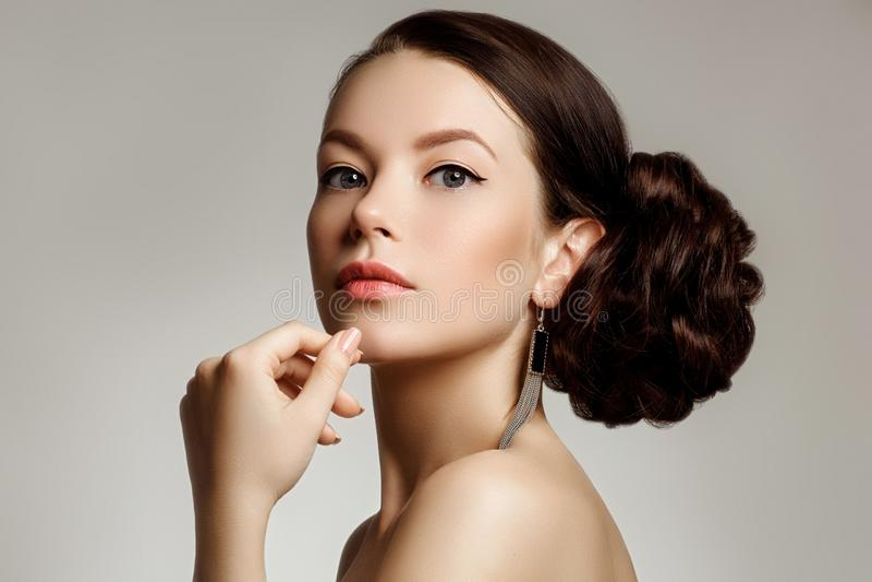 Retrato de una mujer joven hermosa con el peinado creativo imagen de archivo libre de regalías