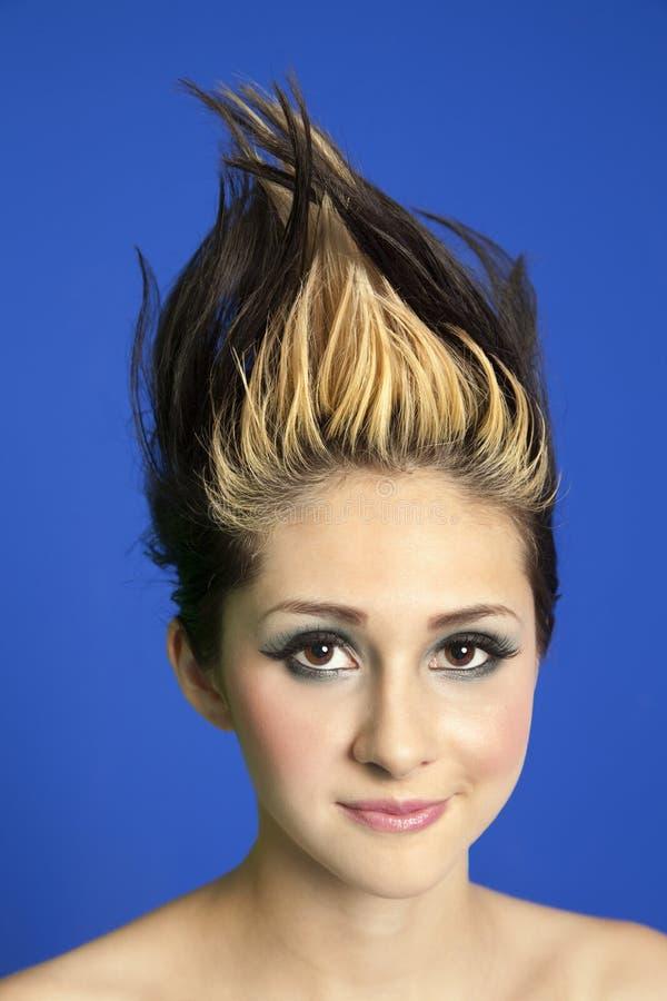 Retrato de una mujer joven hermosa con el pelo claveteado sobre fondo coloreado foto de archivo
