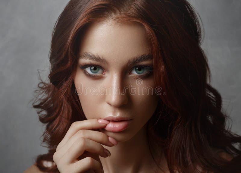 Retrato de una mujer joven hermosa con el pelo del vuelo Muchacha linda que presenta en un fondo gris Ojos hermosos grandes y maq fotografía de archivo