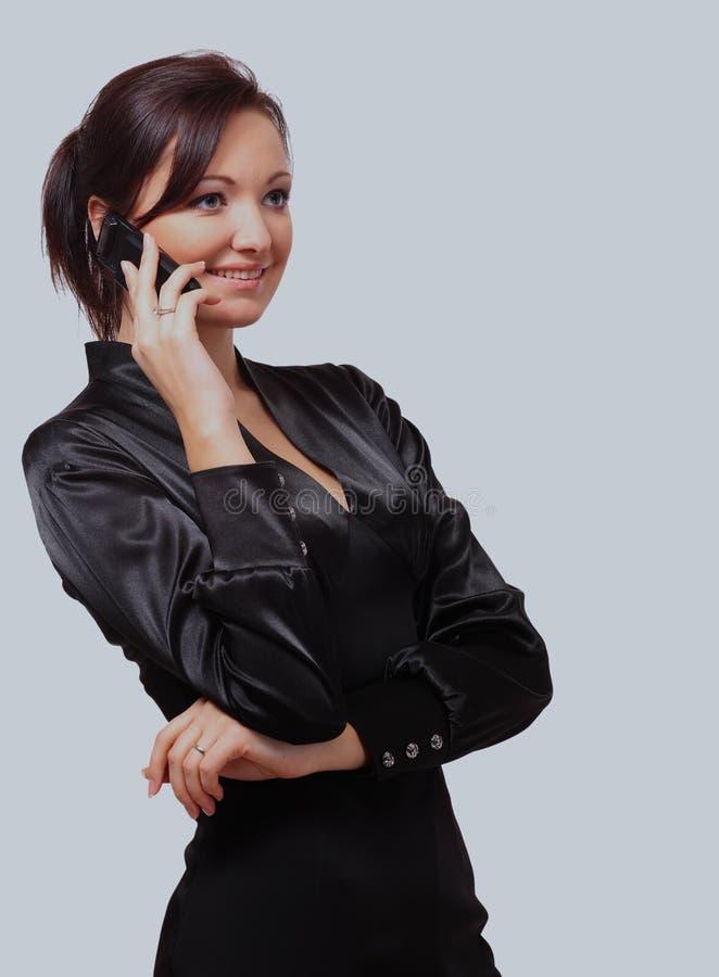 Retrato de una mujer joven hermosa con el teléfono móvil contra el fondo blanco imágenes de archivo libres de regalías