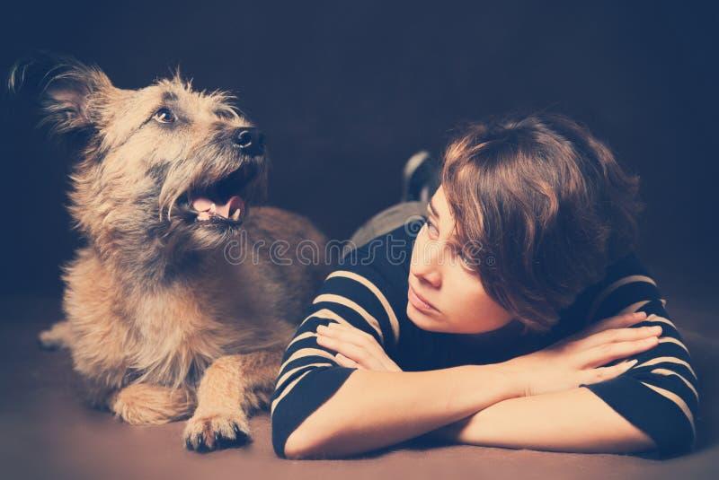 Retrato de una mujer joven hermosa con un perro lanudo divertido en a foto de archivo libre de regalías