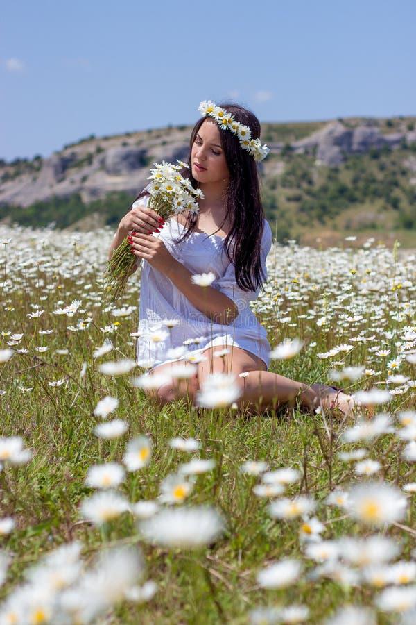 Retrato de una mujer joven hermosa en campo de la manzanilla Muchacha feliz que recoge margaritas Una muchacha que descansa en un imagenes de archivo