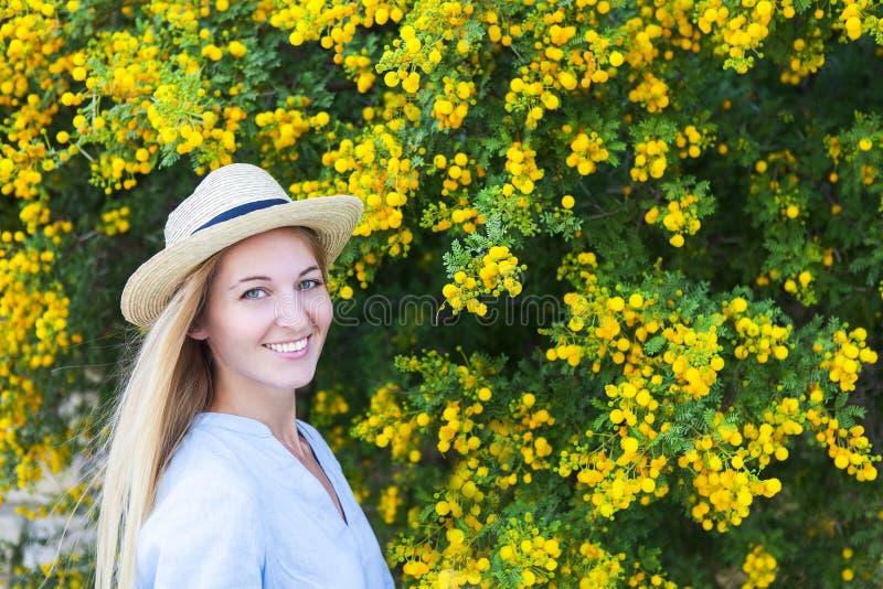 Retrato de una mujer joven hermosa en el sombrero con el flowe de la mimosa fotos de archivo