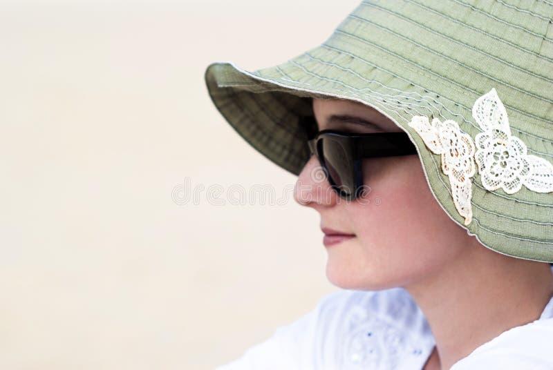 Retrato de una mujer joven hermosa en gafas de sol y sombrero verde foto de archivo libre de regalías