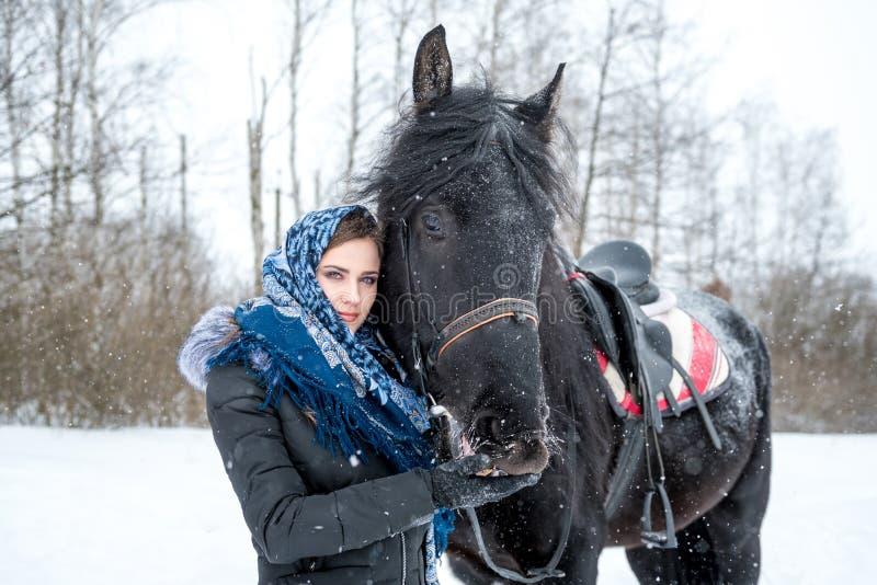Retrato de una mujer joven hermosa en una bufanda azul de moda, fotografía de archivo libre de regalías