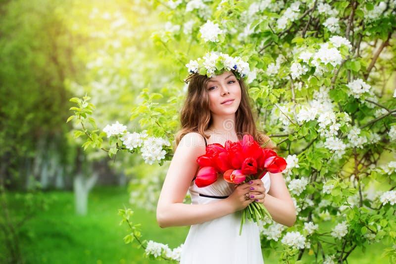 Retrato de una mujer joven hermosa en una guirnalda de la flor de la primavera imagenes de archivo