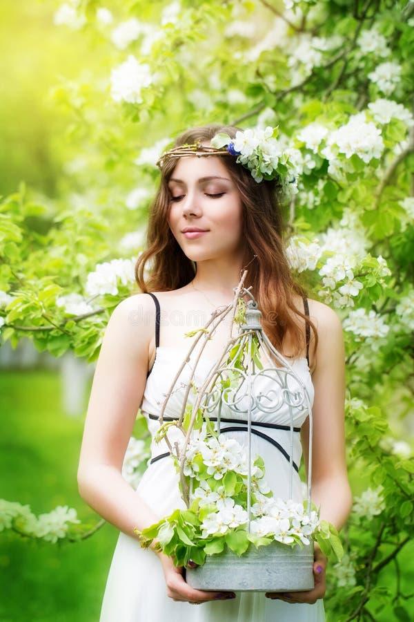 Retrato de una mujer joven hermosa en una guirnalda de la flor de la primavera imagen de archivo