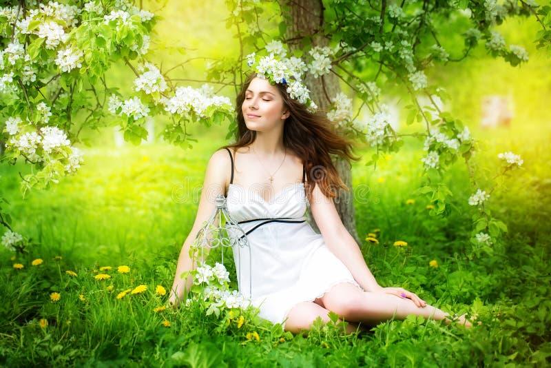 Retrato de una mujer joven hermosa en una guirnalda de la flor de la primavera imagen de archivo libre de regalías