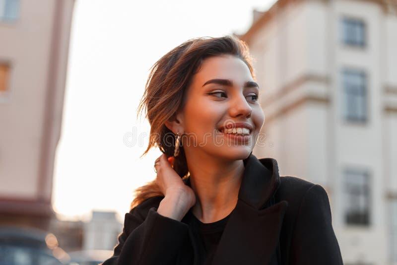 Retrato de una mujer joven hermosa feliz bonita divertida con una sonrisa linda en una capa negra de moda al aire libre en la ciu imagen de archivo